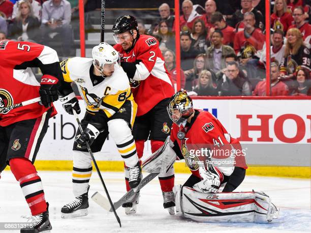 Goaltender Craig Anderson of the Ottawa Senators makes a save while teammate Dion Phaneuf defends against Sidney Crosby of the Pittsburgh Penguins in...