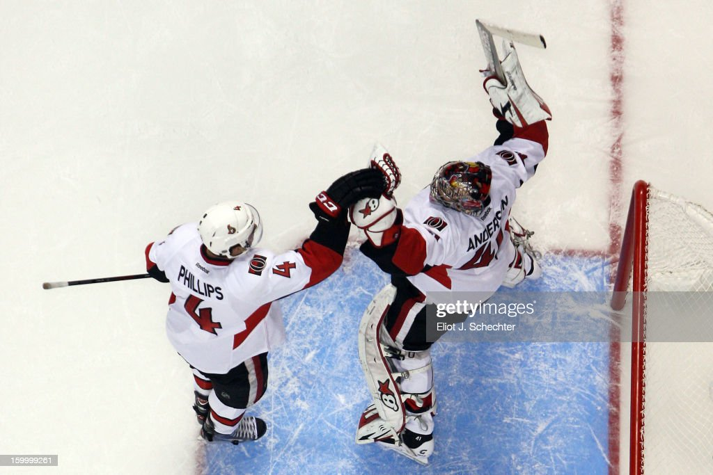 Goaltender <a gi-track='captionPersonalityLinkClicked' href=/galleries/search?phrase=Craig+Anderson&family=editorial&specificpeople=211238 ng-click='$event.stopPropagation()'>Craig Anderson</a> #41of the Ottawa Senators celebrates with teammate Chris Phillips #4 their 3-1 win against the Florida Panthers at the BB&T Center on January 24, 2013 in Sunrise, Florida.