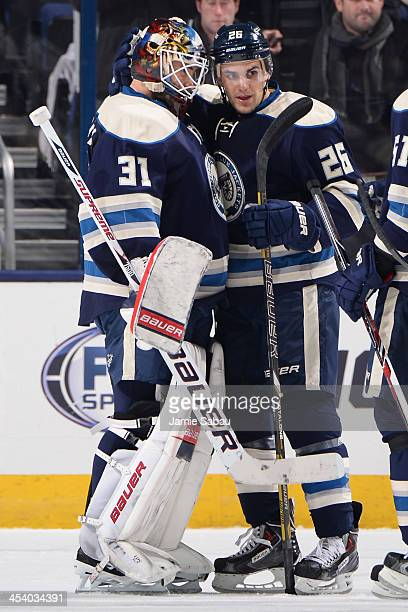 Goaltender Curtis McElhinney of the Columbus Blue Jackets celebrates his shutout against the Minnesota Wild with teammate Corey Tropp of the Columbus...