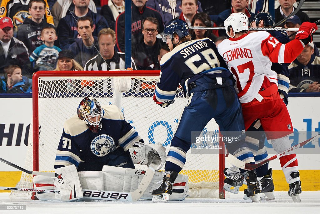 Goaltender <a gi-track='captionPersonalityLinkClicked' href=/galleries/search?phrase=Curtis+McElhinney&family=editorial&specificpeople=2221802 ng-click='$event.stopPropagation()'>Curtis McElhinney</a> #31 of the Columbus Blue Jackets defends the net as teammate <a gi-track='captionPersonalityLinkClicked' href=/galleries/search?phrase=David+Savard&family=editorial&specificpeople=4630692 ng-click='$event.stopPropagation()'>David Savard</a> #58 and <a gi-track='captionPersonalityLinkClicked' href=/galleries/search?phrase=David+Legwand&family=editorial&specificpeople=202553 ng-click='$event.stopPropagation()'>David Legwand</a> #17 of the Detroit Red Wings battle for position during the third period on March 25, 2014 at Nationwide Arena in Columbus, Ohio. Columbus defeated Detroit 4-2.