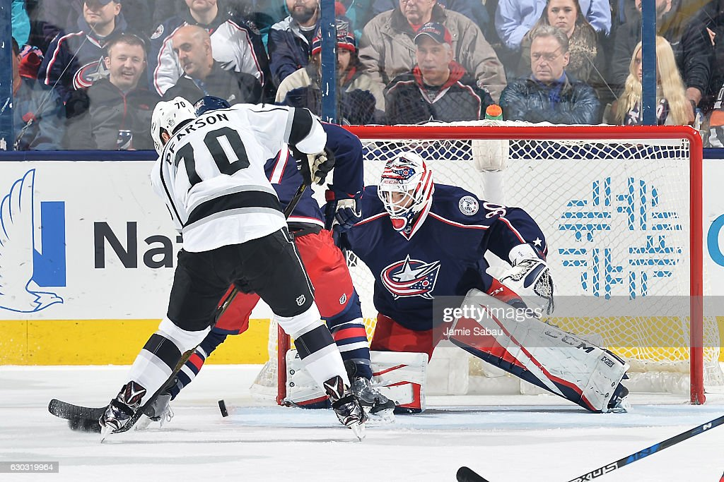 Goaltender Curtis McElhinney #30 of the Columbus Blue Jackets defends the net as Tanner Pearson #70 of the Los Angeles Kings and Ryan Murray #27 of the Columbus Blue Jackets battle for the puck during the first period of a game on December 20, 2016 at Nationwide Arena in Columbus, Ohio.