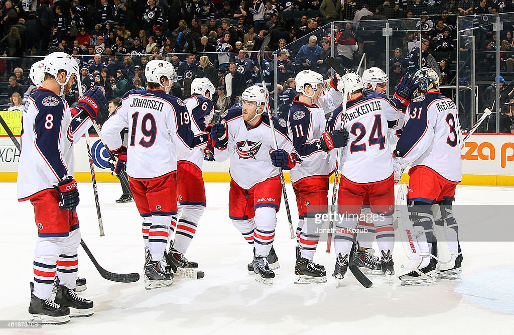 Goaltender <a gi-track='captionPersonalityLinkClicked' href=/galleries/search?phrase=Curtis+McElhinney&family=editorial&specificpeople=2221802 ng-click='$event.stopPropagation()'>Curtis McElhinney</a> #31 of the Columbus Blue Jackets is congratulated by teammates following a 6-3 victory over the Winnipeg Jets at the MTS Centre on January 11, 2014 in Winnipeg, Manitoba, Canada.
