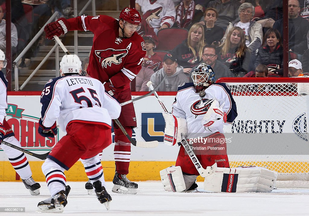 Goaltender Curtis McElhinney #31 of the Columbus Blue Jackets makes a save on the shot as Martin Hanzal #11 of the Phoenix Coyotes looks for a rebound during the second period of the NHL game at Jobing.com Arena on January 2, 2014 in Glendale, Arizona.