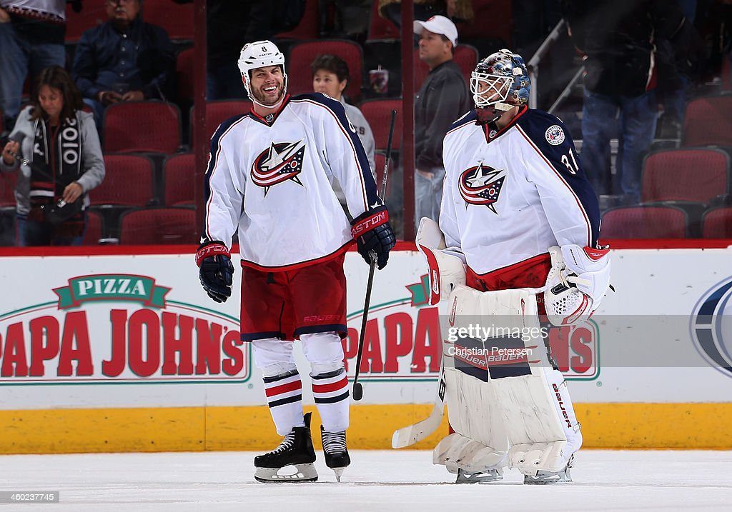 Goaltender <a gi-track='captionPersonalityLinkClicked' href=/galleries/search?phrase=Curtis+McElhinney&family=editorial&specificpeople=2221802 ng-click='$event.stopPropagation()'>Curtis McElhinney</a> #31 of the Columbus Blue Jackets skates off the ice with <a gi-track='captionPersonalityLinkClicked' href=/galleries/search?phrase=Nathan+Horton&family=editorial&specificpeople=204741 ng-click='$event.stopPropagation()'>Nathan Horton</a> #8 following the NHL game against the Phoenix Coyotes at Jobing.com Arena on January 2, 2014 in Glendale, Arizona. The Blue Jackets defeated the Coyotes 2-0.