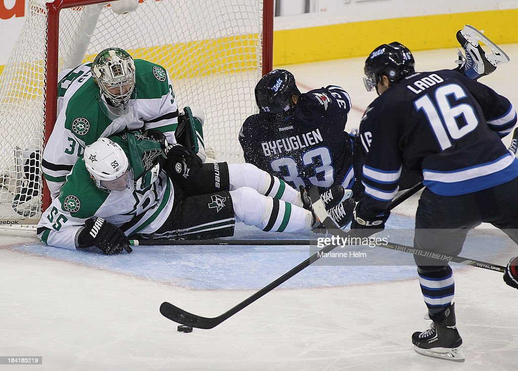 Goaltender <a gi-track='captionPersonalityLinkClicked' href=/galleries/search?phrase=Dan+Ellis&family=editorial&specificpeople=2235265 ng-click='$event.stopPropagation()'>Dan Ellis</a> #30 and <a gi-track='captionPersonalityLinkClicked' href=/galleries/search?phrase=Sergei+Gonchar&family=editorial&specificpeople=202470 ng-click='$event.stopPropagation()'>Sergei Gonchar</a> #55 of the Winnipeg Jets defend the net against the Dallas Stars in third period action of an NHL game at the MTS Centre on October 11, 2013 in Winnipeg, Manitoba, Canada.