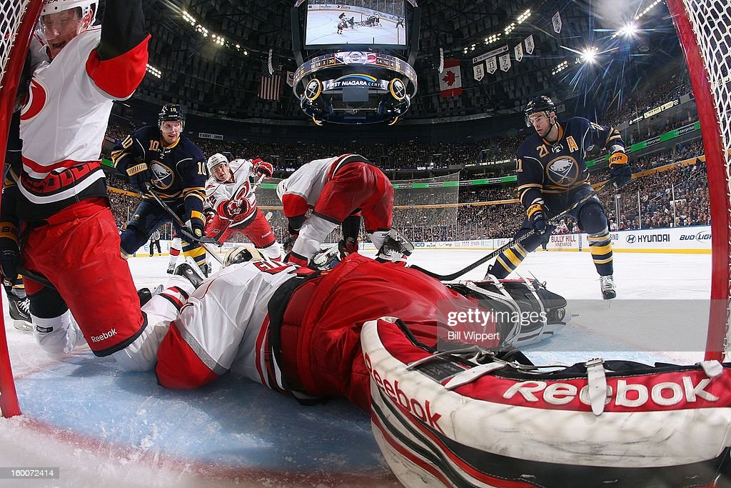 Goaltender <a gi-track='captionPersonalityLinkClicked' href=/galleries/search?phrase=Dan+Ellis&family=editorial&specificpeople=2235265 ng-click='$event.stopPropagation()'>Dan Ellis</a> #31 of the Carolina Hurricanes covers the puck as teammate Joni Pitkanen #25 collides with the goalpost and <a gi-track='captionPersonalityLinkClicked' href=/galleries/search?phrase=Christian+Ehrhoff&family=editorial&specificpeople=214788 ng-click='$event.stopPropagation()'>Christian Ehrhoff</a> #10 and <a gi-track='captionPersonalityLinkClicked' href=/galleries/search?phrase=Drew+Stafford&family=editorial&specificpeople=220617 ng-click='$event.stopPropagation()'>Drew Stafford</a> #21 of the Buffalo Sabres converge on January 25, 2013 at the First Niagara Center in Buffalo, New York.