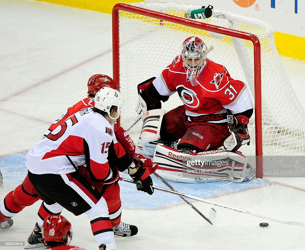 Goaltender <a gi-track='captionPersonalityLinkClicked' href=/galleries/search?phrase=Dan+Ellis&family=editorial&specificpeople=2235265 ng-click='$event.stopPropagation()'>Dan Ellis</a> #31 of the Carolina Hurricanes defends a shot by Zack Smith #15 of the Ottowa Senators during play at PNC Arena on February 1, 2013 in Raleigh, North Carolina. The Hurricanes defeated the Senators, 1-0.