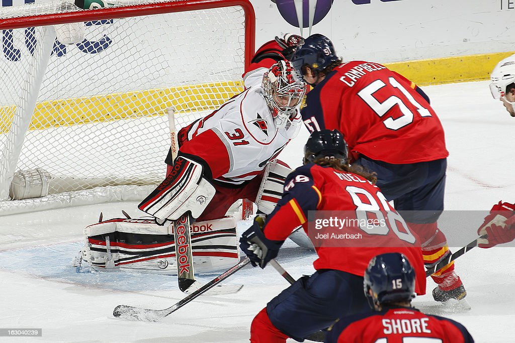 Goaltender <a gi-track='captionPersonalityLinkClicked' href=/galleries/search?phrase=Dan+Ellis&family=editorial&specificpeople=2235265 ng-click='$event.stopPropagation()'>Dan Ellis</a> #31 of the Carolina Hurricanes stops a third period shot by <a gi-track='captionPersonalityLinkClicked' href=/galleries/search?phrase=Brian+Campbell+-+Eishockeyspieler&family=editorial&specificpeople=209384 ng-click='$event.stopPropagation()'>Brian Campbell</a> #51 of the Florida Panthers at the BB&T Center on March 3, 2013 in Sunrise, Florida. The Hurricanes defeated the Panthers 3-2.