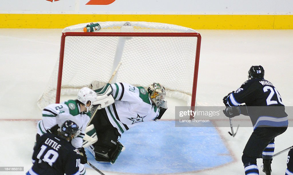 Goaltender Dan Ellis #30 of the Dallas Stars dives across the crease as Blake Wheeler #26 of the Winnipeg Jets shoots the puck into the open net for a third period goal at the MTS Centre on October 11, 2013 in Winnipeg, Manitoba, Canada.