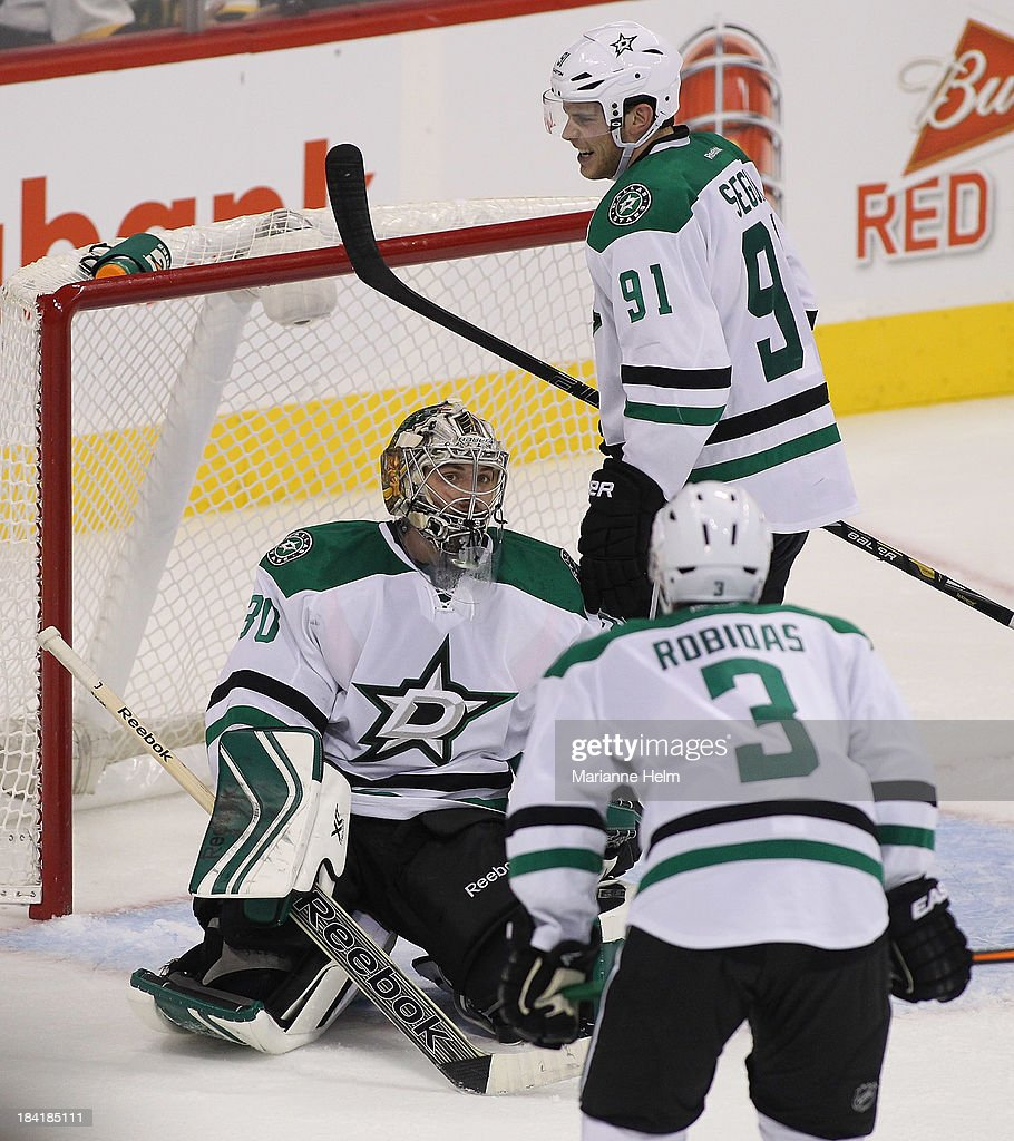 Goaltender <a gi-track='captionPersonalityLinkClicked' href=/galleries/search?phrase=Dan+Ellis&family=editorial&specificpeople=2235265 ng-click='$event.stopPropagation()'>Dan Ellis</a> #30 of the Dallas Stars is met at the net by teammates <a gi-track='captionPersonalityLinkClicked' href=/galleries/search?phrase=Tyler+Seguin&family=editorial&specificpeople=6698848 ng-click='$event.stopPropagation()'>Tyler Seguin</a> #91 and Stephane Robidas #3 at the end of an NHL game against the Winnipeg Jets at the MTS Centre on October 11, 2013 in Winnipeg, Manitoba, Canada. The Stars defeated the Jets 4-1.