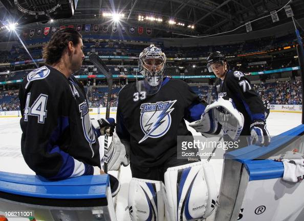 Goaltender Dan Ellis of the Tampa Bay Lightning heads to the bench with teammate Nate Thompson and Victor Hedman before the start of the game against...