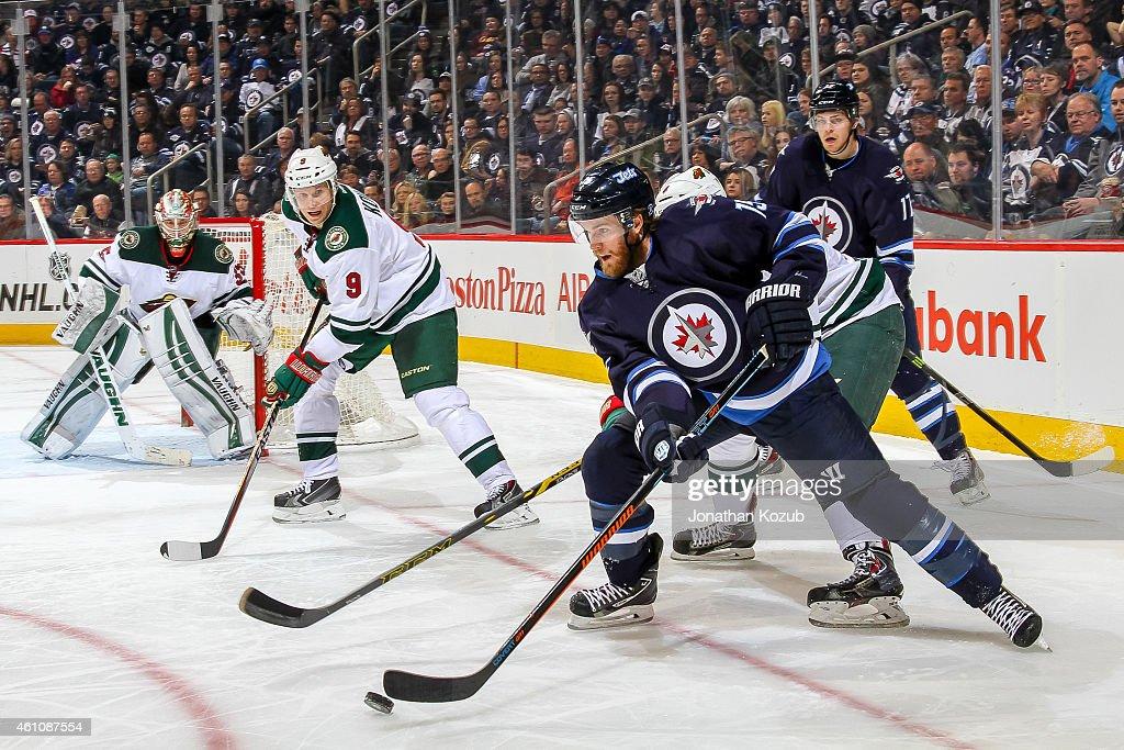Goaltender Darcy Kuemper and Mikko Koivu of the Minnesota Wild keep an eye on Matt Halischuk of the Winnipeg Jets as he plays the puck to the side of...