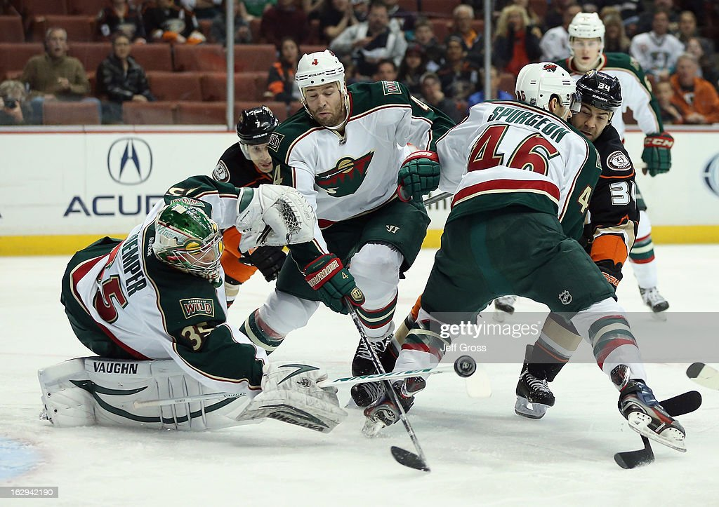 Goaltender Darcy Kuemper #35 of the Minnesota Wild pokes at the puck, as teammates Clayton Stoner #4, Jared Spurgeon #46 defend Daniel Winnik #34 of the Anaheim Ducks in the first period at Honda Center on March 1, 2013 in Anaheim, California.