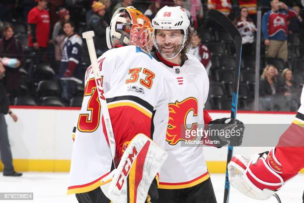 Goaltender David Rittich of the Calgary Flames celebrates a win against the Colorado Avalanche with teammate Jaromir Jagr at the Pepsi Center on...
