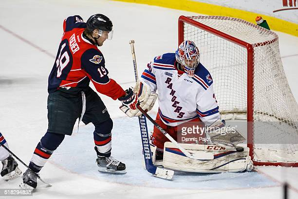 Goaltender Dawson Carty of the Kitchener Rangers makes a glove save against forward Christian Fischer of the Windsor Spitfires during game 4 of the...