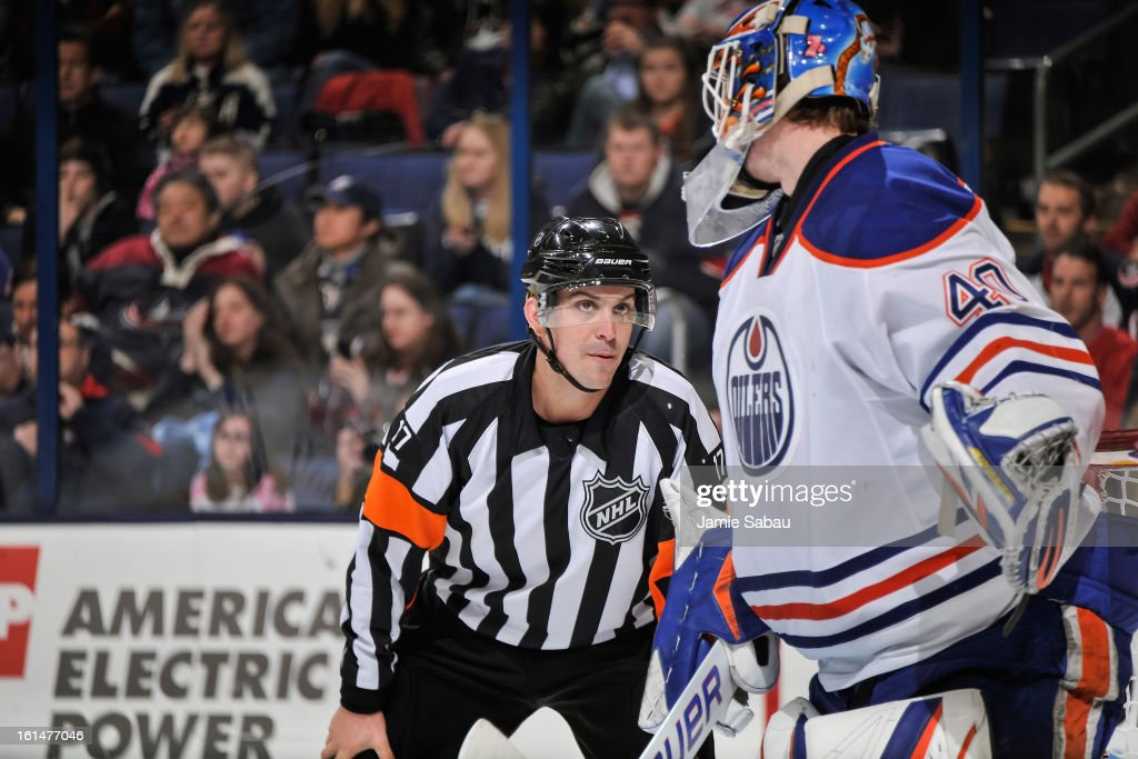Goaltender Devan Dubnyk #40 of the Edmonton Oilers talks with referee Frederick L'Ecuyer #17 during a game against the Columbus Blue Jackets on February 10, 2013 at Nationwide Arena in Columbus, Ohio.