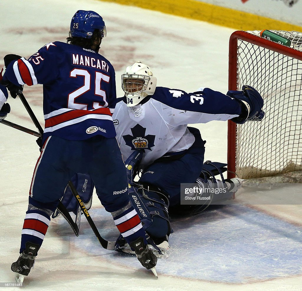 Goaltender Drew MacIntyre makes a behind the back save in front of Mark Mancari as the Toronto Marlies play the Rochester Americans at Ricoh Coliseum.