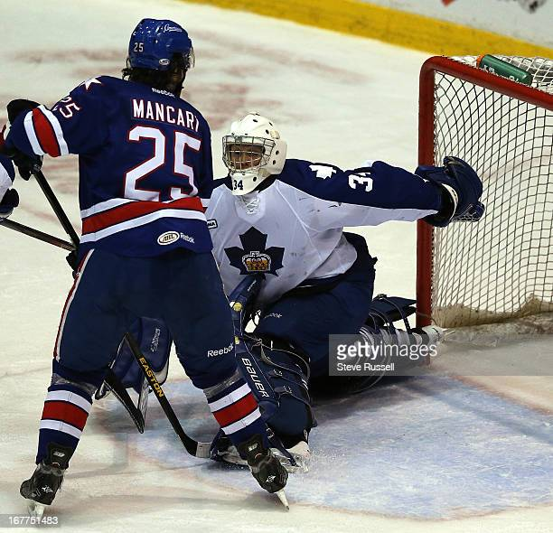 Goaltender Drew MacIntyre makes a behind the back save in front of Mark Mancari as the Toronto Marlies play the Rochester Americans at Ricoh Coliseum