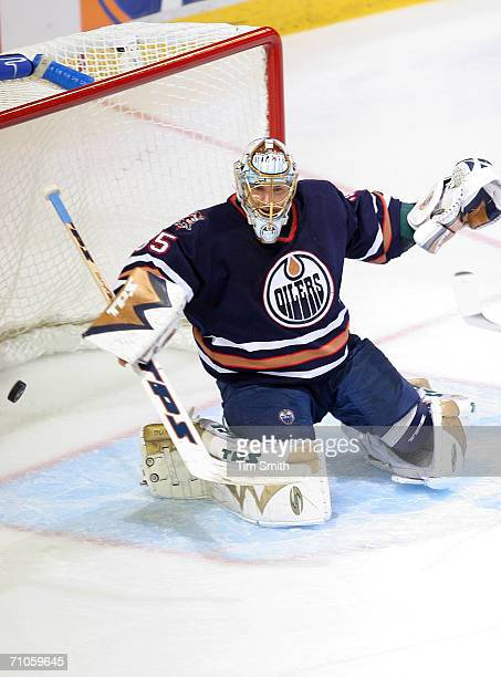 Goaltender Dwayne Roloson of the Edmonton Oilers protect the goal against the defense of the Mighty Ducks of Anaheim during game four of the Western...