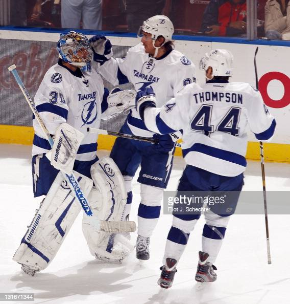 Goaltender Dwayne Roloson of the Tampa Bay Lightning celebrates their shootout win with teammates Matt Gilroy and Nate Thompson against the Florida...