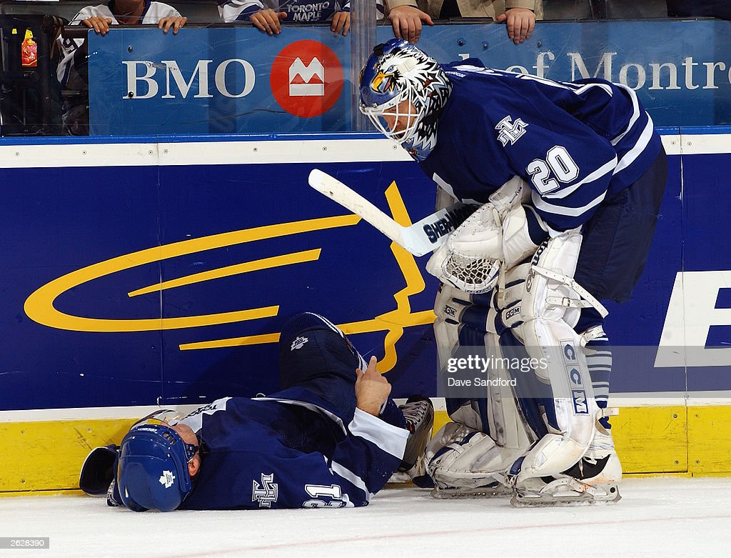 Goaltender Ed Belfour #20 of the Toronto Maple Leafs checks on teammate Robert Reichel #21 as he lays injured on the ice against the Washington Capitals during their NHL game on October 13, 2003 at Air Canada Centre in Toronto, Ontario, Canada. The Maple Leafs and the Capitals skated to a 2-2 tie.