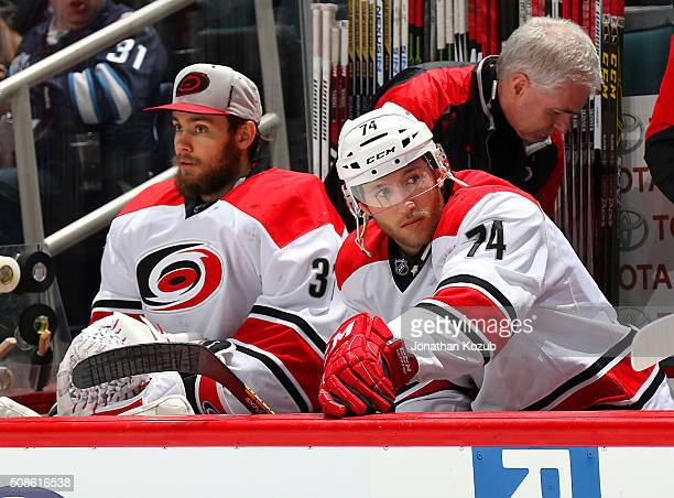 Goaltender Eddie Lack and Jaccob Slavin of the Carolina Hurricanes look on from the bench prior to puck drop against the Winnipeg Jets at the MTS...