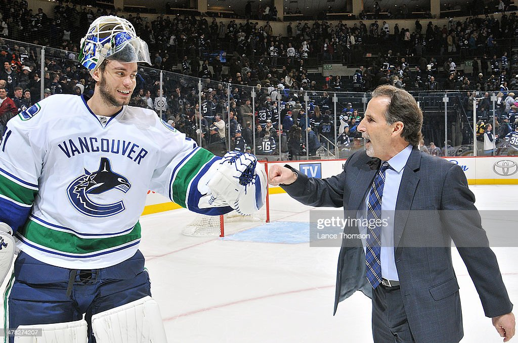 Goaltender Eddie Lack #31 of the Vancouver Canucks gets a congratulatory fist bump from Head Coach <a gi-track='captionPersonalityLinkClicked' href=/galleries/search?phrase=John+Tortorella&family=editorial&specificpeople=213393 ng-click='$event.stopPropagation()'>John Tortorella</a> after backstopping the team to a 3-2 shootout victory over the Winnipeg Jets at the MTS Centre on March 12, 2014 in Winnipeg, Manitoba, Canada.
