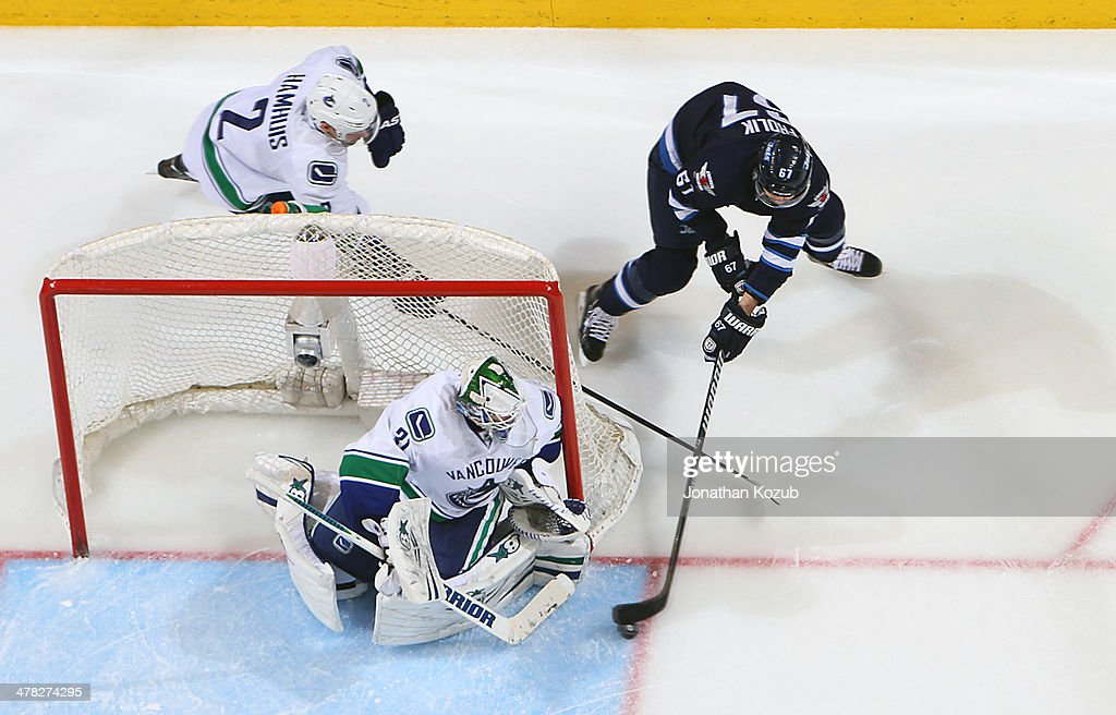 Goaltender Eddie Lack #31 of the Vancouver Canucks guards the net as <a gi-track='captionPersonalityLinkClicked' href=/galleries/search?phrase=Michael+Frolik&family=editorial&specificpeople=537965 ng-click='$event.stopPropagation()'>Michael Frolik</a> #67 of the Winnipeg Jets tries to score on a wrap-around attempt during third period action at the MTS Centre on March 12, 2014 in Winnipeg, Manitoba, Canada.