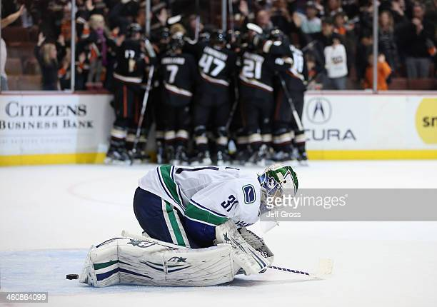 Goaltender Eddie Lack of the Vancouver Canucks looks dejected as the Anaheim Ducks celebrate Corey Perry's game winning goal in overtime at Honda...
