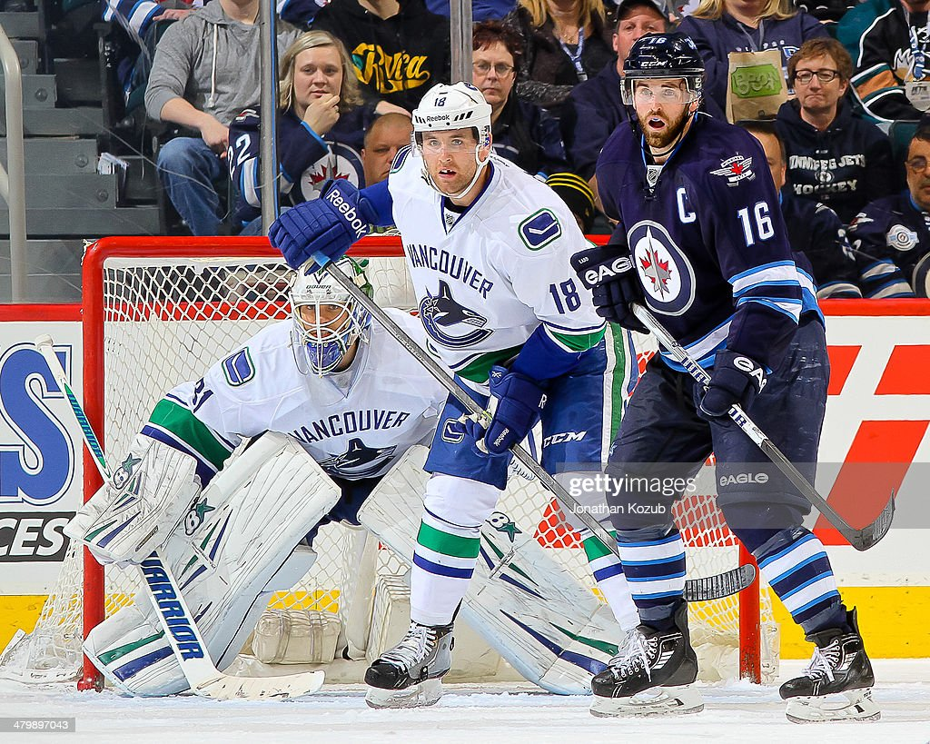 Goaltender Eddie Lack Ryan Stanton of the Vancouver Canucks and Andrew Ladd of the Winnipeg Jets keep an eye on the play during second period action...