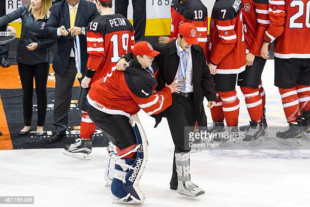 Goaltender Eric Comrie of Canada assists injured teammate Robby Fabri after a 54 win against Russia during the Gold medal game of the 2015 IIHF World...