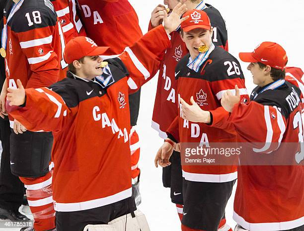 Goaltender Eric Comrie of Canada celebrates with teammate goaltender Zach Fucale after a 54 win against Russia during the Gold medal game of the 2015...