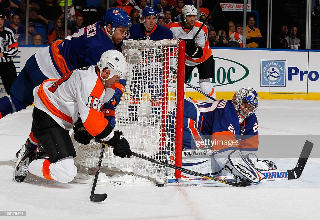 Goaltender Evgeni Nabokov #20 and Matt Carkner #7 of the New York Islanders defend the net against Adam Hall #18 of the Philadelphia Flyers at Nassau Veterans Memorial Coliseum on April 9, 2013 in Uniondale, New York.