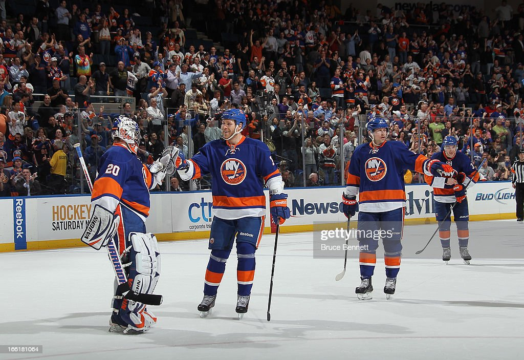 Goaltender Evgeni Nabokov #20 and Matt Carkner #7 of the New York Islanders celebrate their 4-1 victory over the Philadelphia Flyers at the Nassau Veterans Memorial Coliseum on April 9, 2013 in Uniondale, New York.