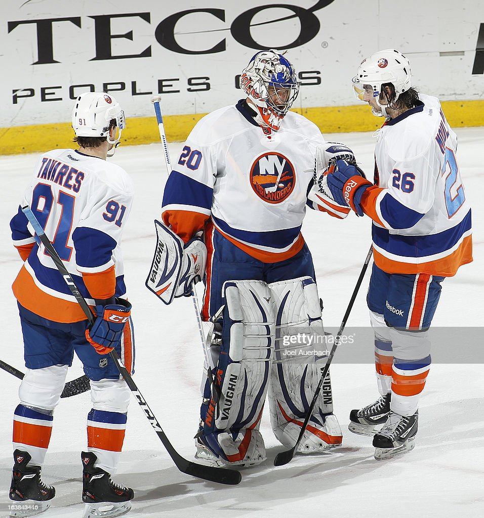 Goaltender Evgeni Nabokov #20 is congratulated by John Tavares #91 and Matt Moulson #26 of the New York Islanders at the end of the game against the Florida Panthers at the BB&T Center on March 16, 2013 in Sunrise, Florida. The Islanders defeated the Panthers 4-3.
