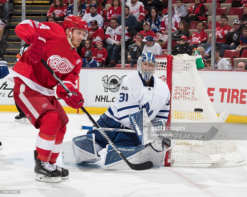 Goaltender Frederik Andersen #31 of the Toronto Maple Leafs bats the puck away as Gustav Nyquist #14 of the Detroit Red Wings look for the rebound during an NHL game at Joe Louis Arena on January 25, 2017 in Detroit, Michigan.