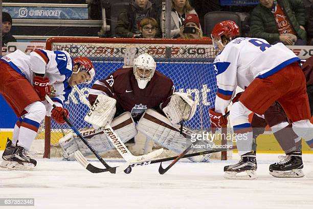 Goaltender Gustavs Grigals of Team Latvia anticipates Forward German Rubstov of Team Russia shot on net in a preliminary game during the IIHF World...