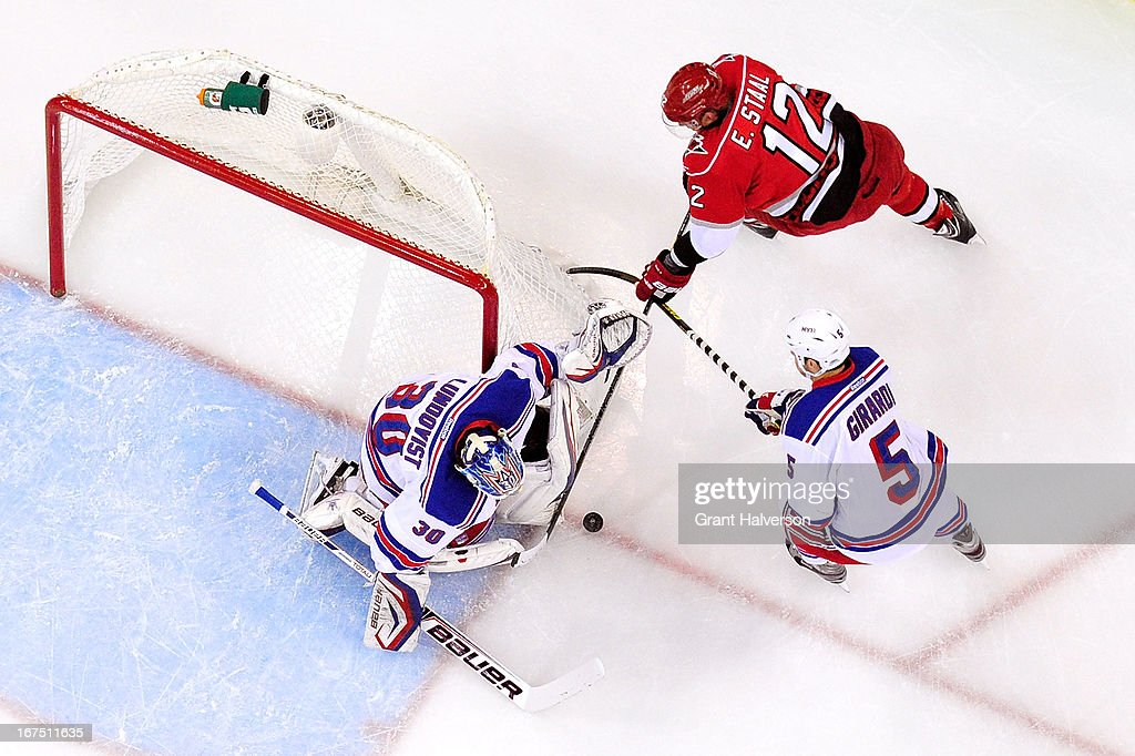 Goaltender Henrik Lundqvist #30 and Dan Girardi #5 of the New York Rangers stop a shot by Eric Staal #12 of the Carolina Hurricanes during play at PNC Arena on April 25, 2013 in Raleigh, North Carolina. The Rangers won 4-3 in overtime.