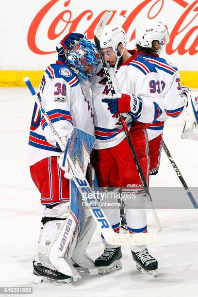 Goaltender Henrik Lundqvist of the New York Rangers celebrates with teammate Mika Zibanejad their 52 win over the Florida Panthers at the BBT Center...