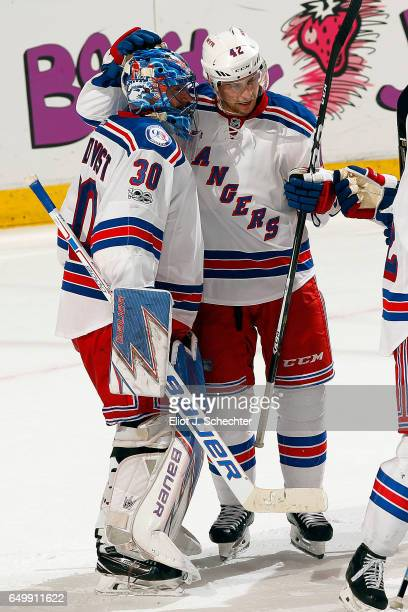 Goaltender Henrik Lundqvist of the New York Rangers celebrates with teammate Brendan Smith their 52 win over the Florida Panthers at the BBT Center...