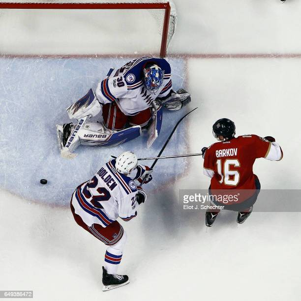 Goaltender Henrik Lundqvist of the New York Rangers defends the net with the help of teammate Nick Holden against Aleksander Barkov of the Florida...