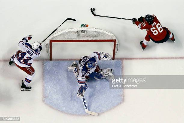 Goaltender Henrik Lundqvist of the New York Rangers defends the net with the help of teammate Brendan Smith against Jaromir Jagr of the Florida...