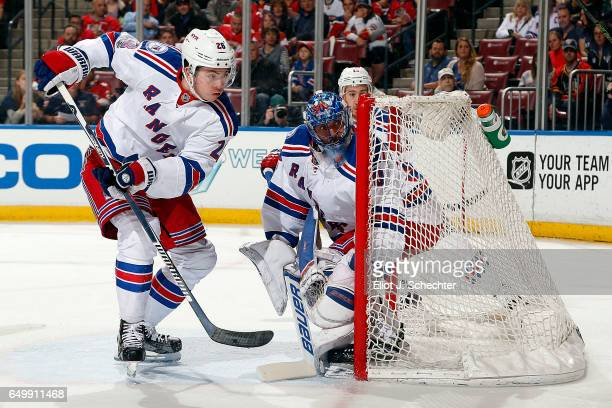 Goaltender Henrik Lundqvist of the New York Rangers defends the net with the help of teammate Jimmy Vesey against the Florida Panthers at the BBT...