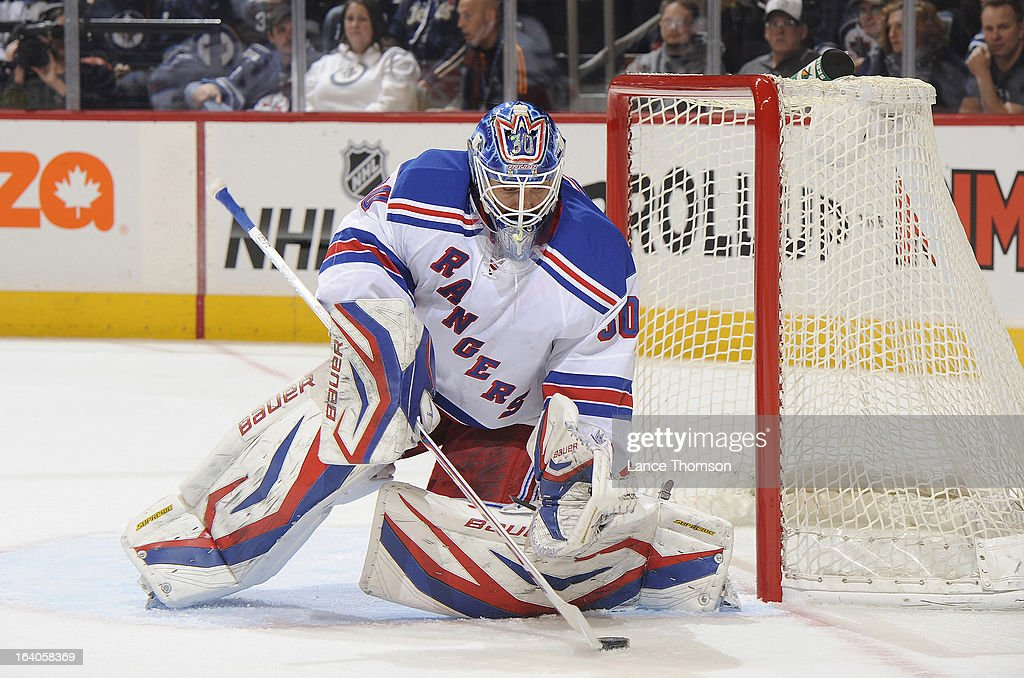 Goaltender Henrik Lundqvist #30 of the New York Rangers handles the puck beside the net during first period action against the Winnipeg Jets at the MTS Centre on March 14, 2013 in Winnipeg, Manitoba, Canada. The Jets defeated the Rangers 3-1.
