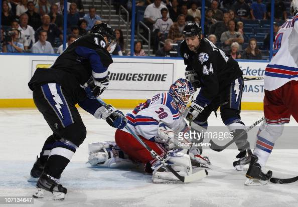 Goaltender Henrik Lundqvist of the New York Rangers kicks the puck away from Sean Bergenheim and Nate Thompson of the Tampa Bay Lightning during the...