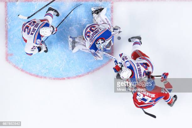 Goaltender Henrik Lundqvist of the New York Rangers makes a save while teammate Oscar Lindberg battles for position with Alex Galchenyuk of the...