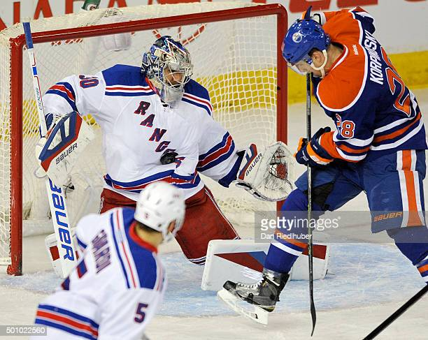 goaltender Henrik Lundqvist of the New York Rangers makes a save with Lauri Korpikoski of the Edmonton Oilers looking for a rebound at Rexall Place...