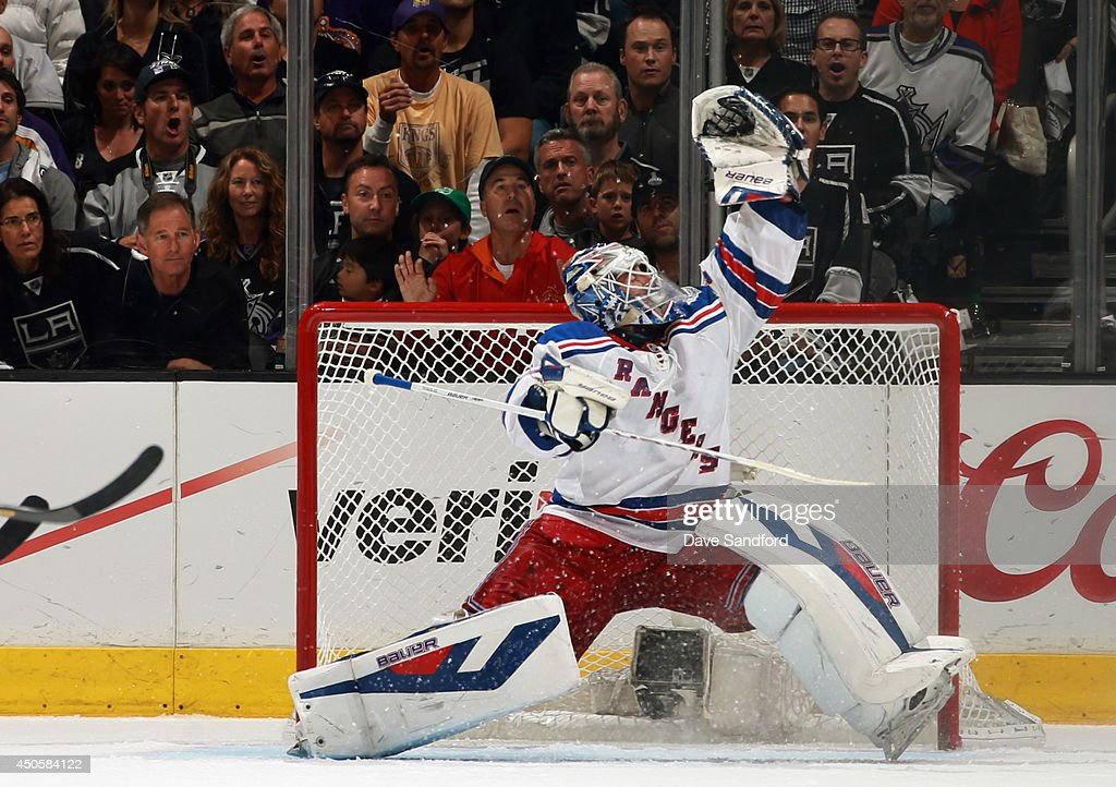 Goaltender Henrik Lundqvist of the New York Rangers reaches for the puck in the third period of Game Five of the 2014 Stanley Cup Final against the...