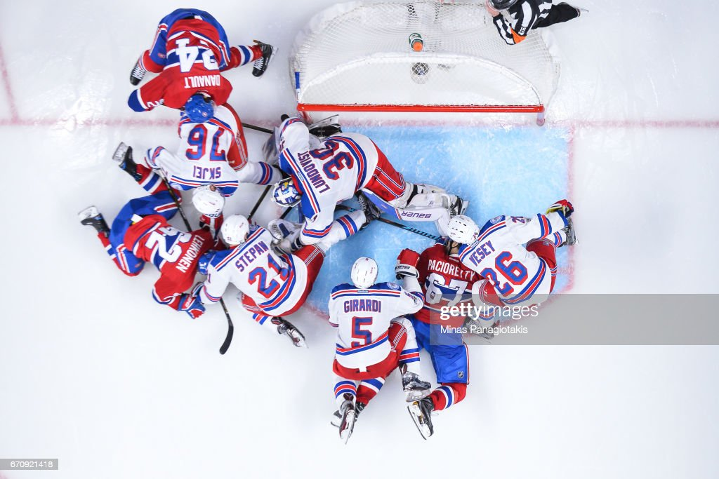 Goaltender Henrik Lundqvist #30 of the New York Rangers tries to cover the puck with a pileup of players around him against the Montreal Canadiens in Game Five of the Eastern Conference First Round during the 2017 NHL Stanley Cup Playoffs at the Bell Centre on April 20, 2017 in Montreal, Quebec, Canada. The New York Rangers defeated the Montreal Canadiens 3-2 in overtime.