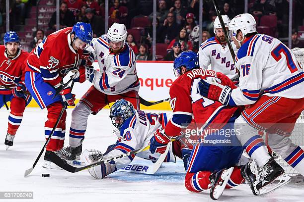 Goaltender Henrik Lundqvist of the New York Rangers tries to grab the puck from Brian Flynn of the Montreal Canadiens during the NHL game at the Bell...